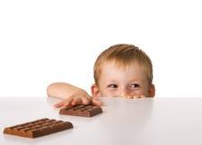 Das Kind und eine Schokolade stockbilder
