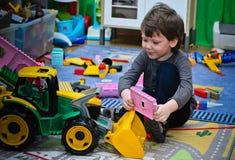Das Kind und sein Spielzeugtraktor lizenzfreie stockbilder