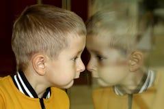Das Kind untersucht den Speicher durch das Glas Reflexion auf Glas stockfotos