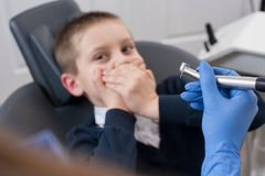 Das Kind, das von den Zahnärzten erschrocken wird, bedeckt seinen Mund und Zahnarzt in den Handschuhen, die in der Hand Zahnbohre stockbilder