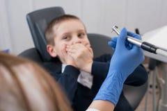 Das Kind, das von den Zahnärzten erschrocken wird, bedeckt seinen Mund und Zahnarzt in den Handschuhen, die in der Hand Zahnbohre stockfoto