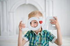 Das Kind, welches die Buchstabeliebe und -c$lächeln hält Lizenzfreies Stockbild