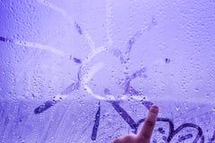 Das Kind zeichnet die Sonne am misted und nassen Fenster lizenzfreies stockfoto