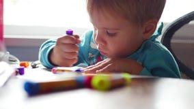 Das Kind zeichnet enthusiastisch mit Zeichenstiften auf einem Blatt Papier Vorschulbildung stock video