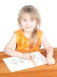 Das Kind zeichnet am Tisch Lizenzfreie Stockfotos
