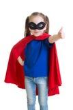 Das Kind zeigt Daumen oben vortäuschend, ein Superheld zu sein stockfotografie