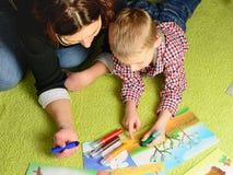 Das Kind zusammen mit Mutter zeichnet ein Bild Stockfoto