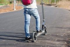 Das Kindermädchen geht auf eine Reise auf dem Roller Lizenzfreies Stockfoto