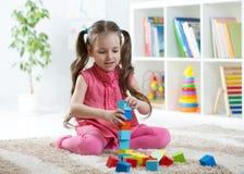 Das Kindermädchen, das mit Block spielt, spielt in der Kindertagesstättenmitte Lizenzfreie Stockfotografie