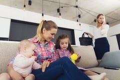 Das Kindermädchen spielt mit dem Mädchen und dem Baby auf der Couch Sie haben Spaß Lizenzfreie Stockfotografie