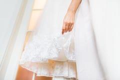 Das Kleid und die Hand der Braut am Hochzeitstag Stockbild