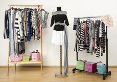 Das Kleiden des Wandschranks mit gestreifter Kleidung vereinbarte auf Aufhängern. Stockfotografie