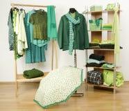 Das Kleiden des Wandschranks mit grüner Kleidung vereinbarte auf Aufhängern und Regal Lizenzfreie Stockbilder
