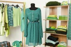 Das Kleiden des Wandschranks mit grüner Kleidung vereinbarte auf Aufhängern und Regal, kleiden auf einem Mannequin an. Stockfotos
