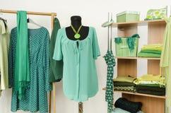 Das Kleiden des Wandschranks mit grüner Kleidung vereinbarte auf Aufhängern und Regal, statten auf einem Mannequin aus Lizenzfreies Stockfoto