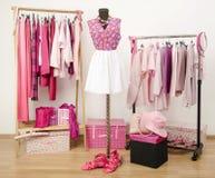 Das Kleiden des Wandschranks mit rosa Kleidung vereinbarte auf Aufhängern und einer Ausstattung auf einem Mannequin. Lizenzfreie Stockbilder