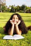 Das kleine afrikanische Mädchen, das auf ein Gras im Park mit Buch legt Lizenzfreies Stockfoto