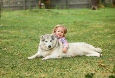 Das kleine Baby, das mit Hund gegen grünes Gras spielt Lizenzfreie Stockfotografie