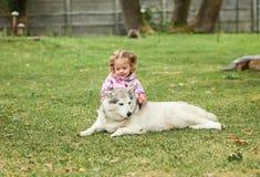 Das kleine Baby, das mit Hund gegen grünes Gras spielt Stockbild