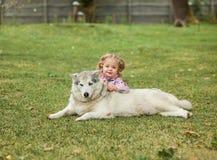 Das kleine Baby, das mit Hund gegen grünes Gras spielt Stockfotografie