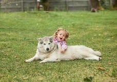 Das kleine Baby, das mit Hund gegen grünes Gras spielt Stockfoto