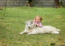 Das kleine Baby, das mit Hund gegen grünes Gras spielt Lizenzfreie Stockfotos
