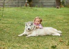 Das kleine Baby, das mit Hund gegen grünes Gras spielt Stockfotos