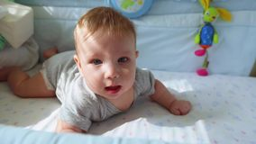 Das kleine Baby im Krippenlachen und -versuchen zu kriechen Glückliche Kindheit, kindische Freude, die ersten Schritte im Leben stock video footage
