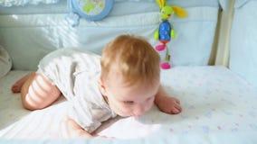 Das kleine Baby im Krippenlachen und -versuchen zu kriechen Glückliche Kindheit, kindische Freude, die ersten Schritte im Leben stock video