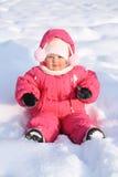 Das kleine frohe Mädchen sitzt in einem Schnee Stockfoto