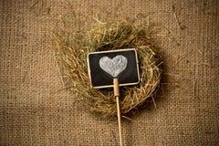 Das kleine Herz, das auf die Tafel liegt in den Vögeln gezeichnet wird, nisten stockbild