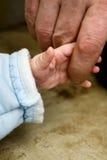 Das kleine Kind, das für einen Finger des Vaters hält Stockfoto