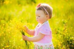 Das kleine Kind, das mit Feld spielt, blüht am Frühlings- oder Sommertag Stockfotografie