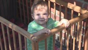 Das kleine Kind lacht in einer Krippe stock footage