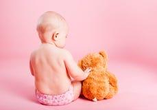 Das kleine Kind mit einem Bärenjungen Lizenzfreie Stockfotografie