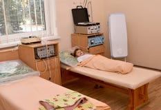 Das kleine kranke Mädchen liegt auf einer Couch in einem physiotherapeutischen offi Stockbild