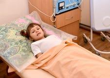Das kleine kranke Mädchen liegt auf einer Couch in einem physiotherapeutischen offi Lizenzfreie Stockbilder