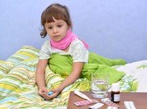 Das kleine kranke Mädchen sitzt in einem Bett Lizenzfreie Stockfotos