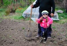 Das kleine Mädchen arbeitet im Garten Lizenzfreie Stockbilder