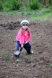 Das kleine Mädchen arbeitet im Garten Lizenzfreies Stockbild