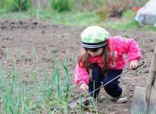 Das kleine Mädchen arbeitet im Garten Lizenzfreie Stockfotos
