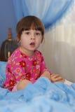 Das kleine Mädchen auf einem Bett Stockbilder
