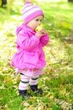 Das kleine Mädchen auf einer Lichtung mit einem Apfel Lizenzfreies Stockfoto