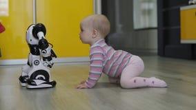 Das kleine Mädchen betrachtet sorgfältig den Spielzeugroboter und -tänze mit ihm Moderne Robotertechnologien