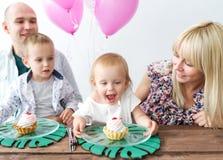 Das kleine Mädchen brennt heraus die Kerze durch Glückliche Familie, die einen Geburtstagsfeiergeburtstag der Tochter feiert lizenzfreies stockfoto