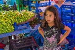 Das kleine Mädchen, das öffentlich Markt des Gemüses verkauft Stockfoto