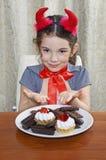 Das kleine Mädchen, das als Teufel gekleidet wird, isst Bonbons am Tisch Stockbilder