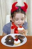 Das kleine Mädchen, das als Teufel gekleidet wird, isst Kuchen am Tisch Lizenzfreies Stockbild