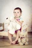 Das kleine Mädchen, das auf dem Bett mit Plüsch sitzt, spielt Lizenzfreie Stockbilder