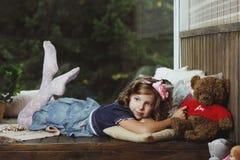 Das kleine Mädchen, das auf einer Holzkiste liegt Lizenzfreies Stockfoto